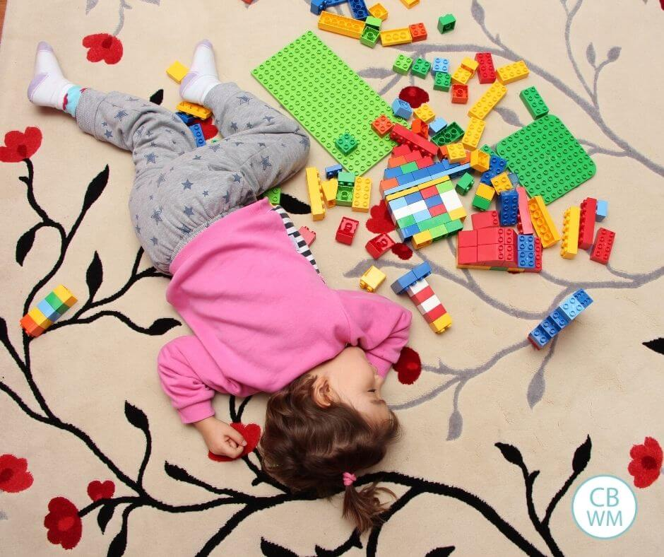 toddler sleeping on floor with LEGOs