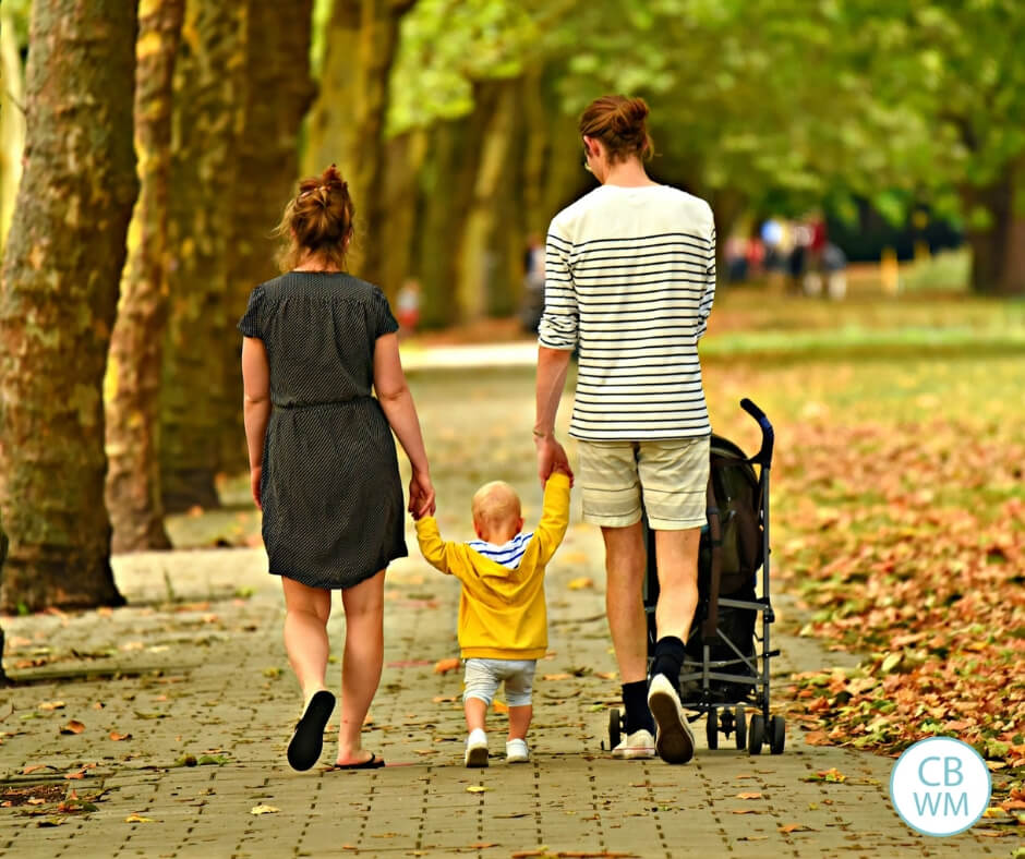 Parents walking with their first born child.