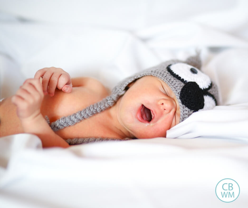 Baby sleeping in a hat on white bedding with mouth open