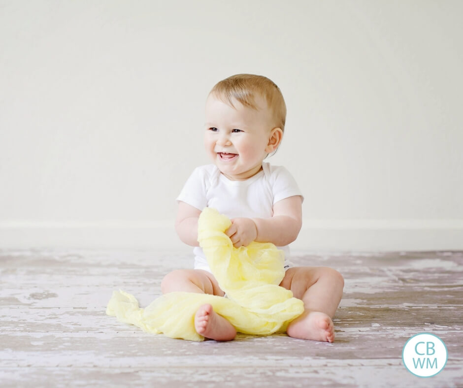 Cute Pretoddler smiling as he/she plays with yellow fabric