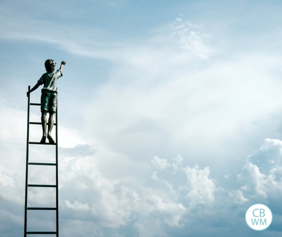 Child reaching for the clouds while standing on a ladder