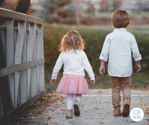 Boy and girl walking across a bridge together