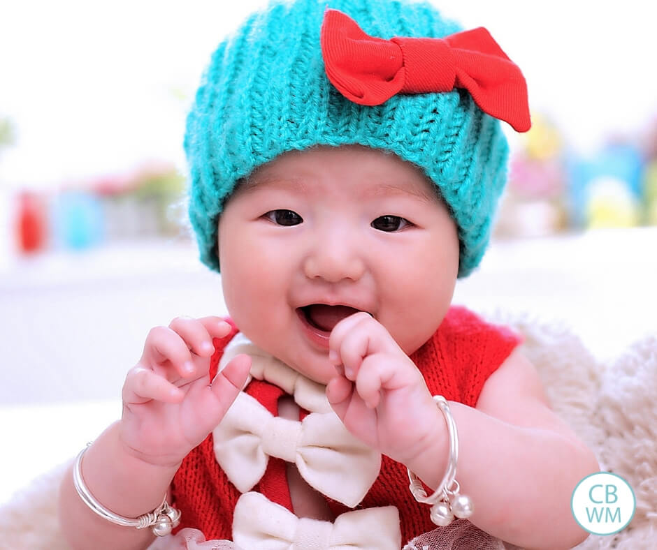 Baby girl with blue hat and a red shirt