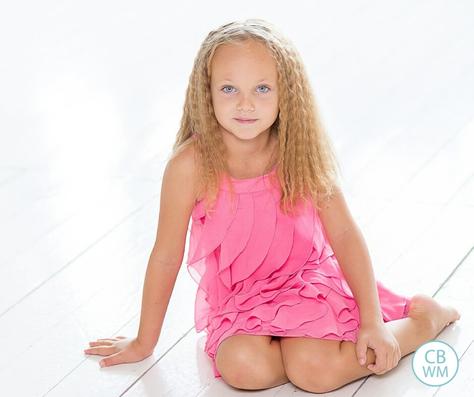 Girl in a pink dress sitting on the floor