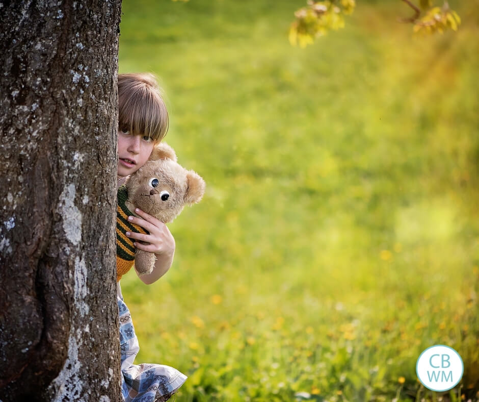 A girl hiding behind a tree holding a bear