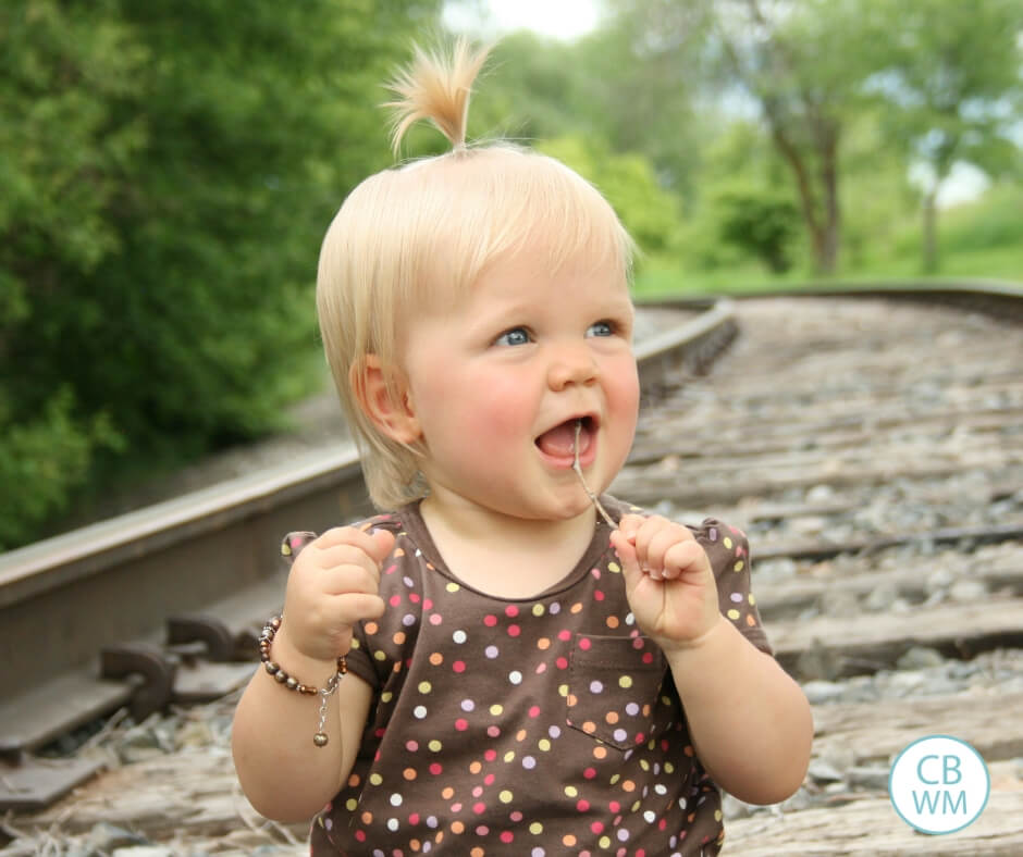 Toddler girl sitting on the train tracks
