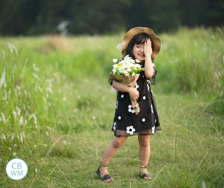 Girl standing in a green meadow holding a bouquet of flowers