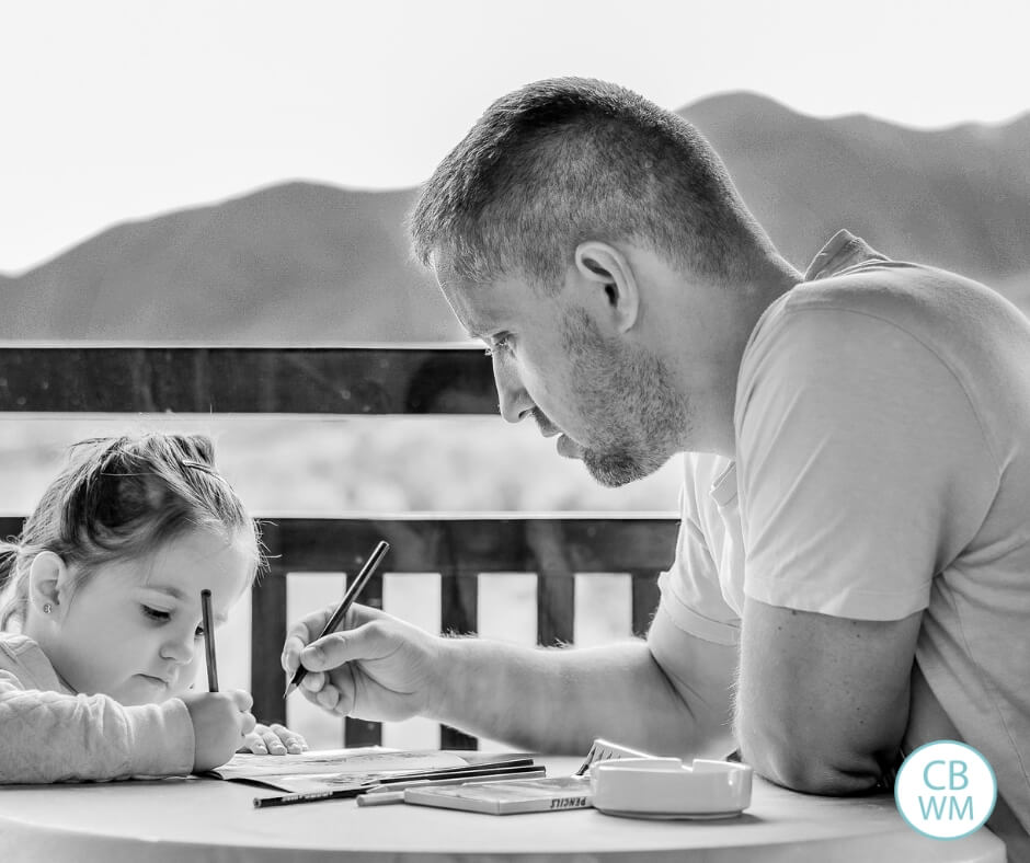 black and white photo of a dad and daughter writing together