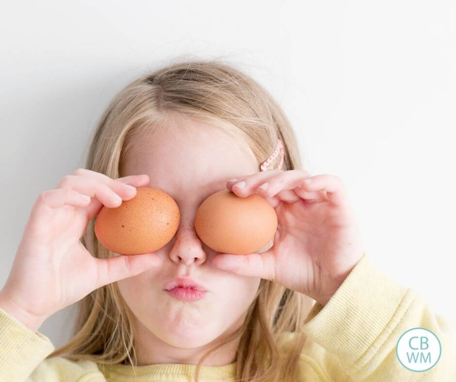 Girl holding eggs over her eyes