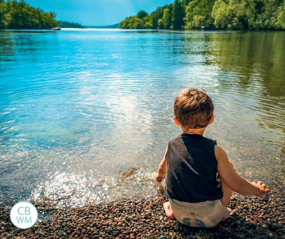 boy sitting on shore of the lake