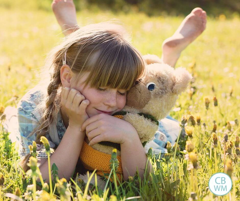 Girl hugging a stuffed animal on the grass