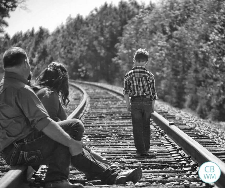 Child walking down the railroad tracks as parent watch