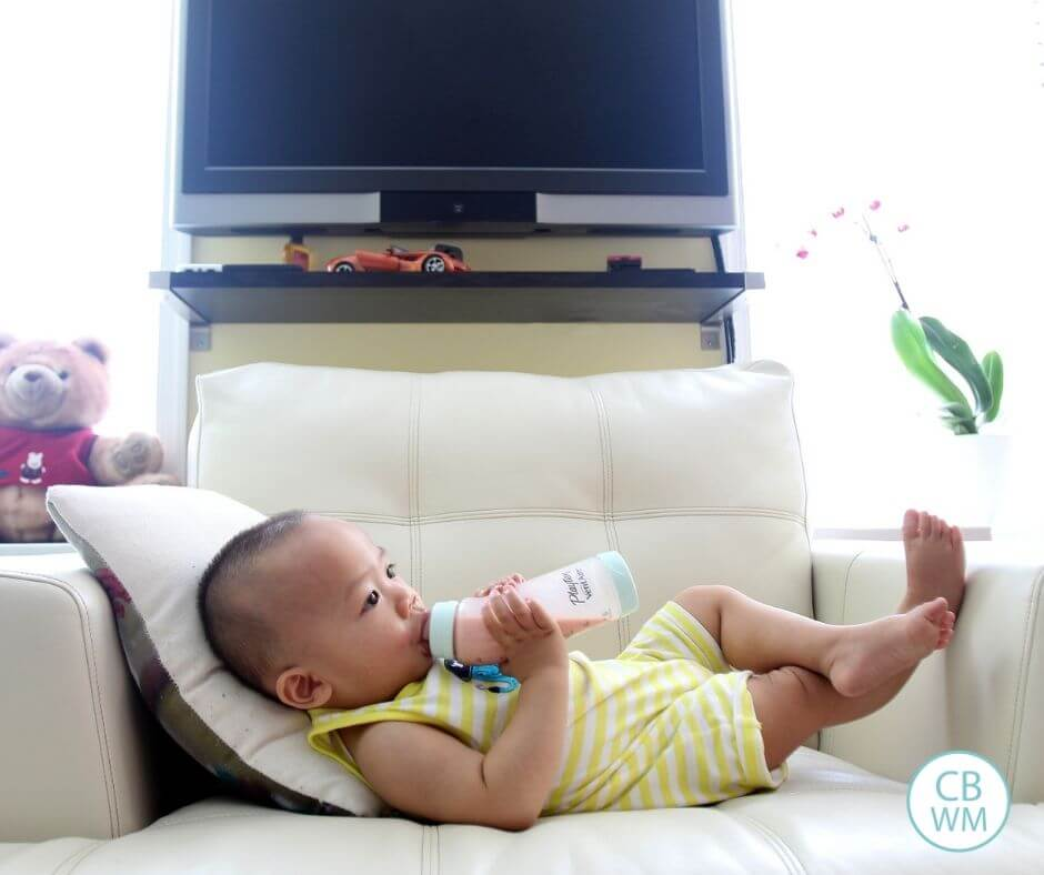 Baby drinking milk from a bottle on the couch