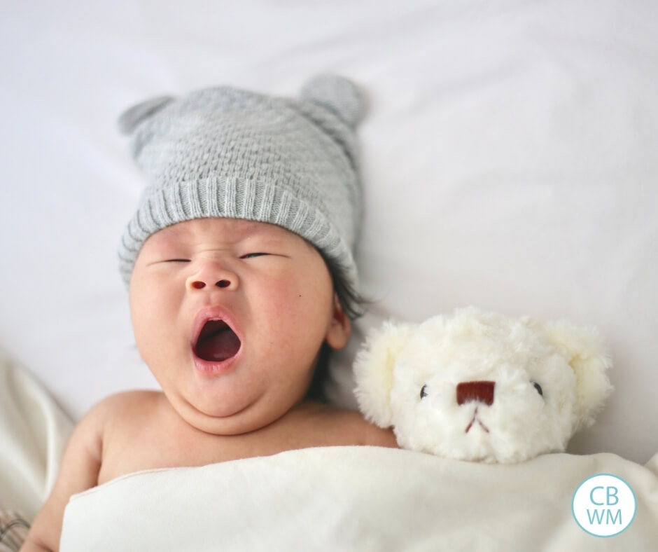 Baby yawning in bed next to a teddy bear