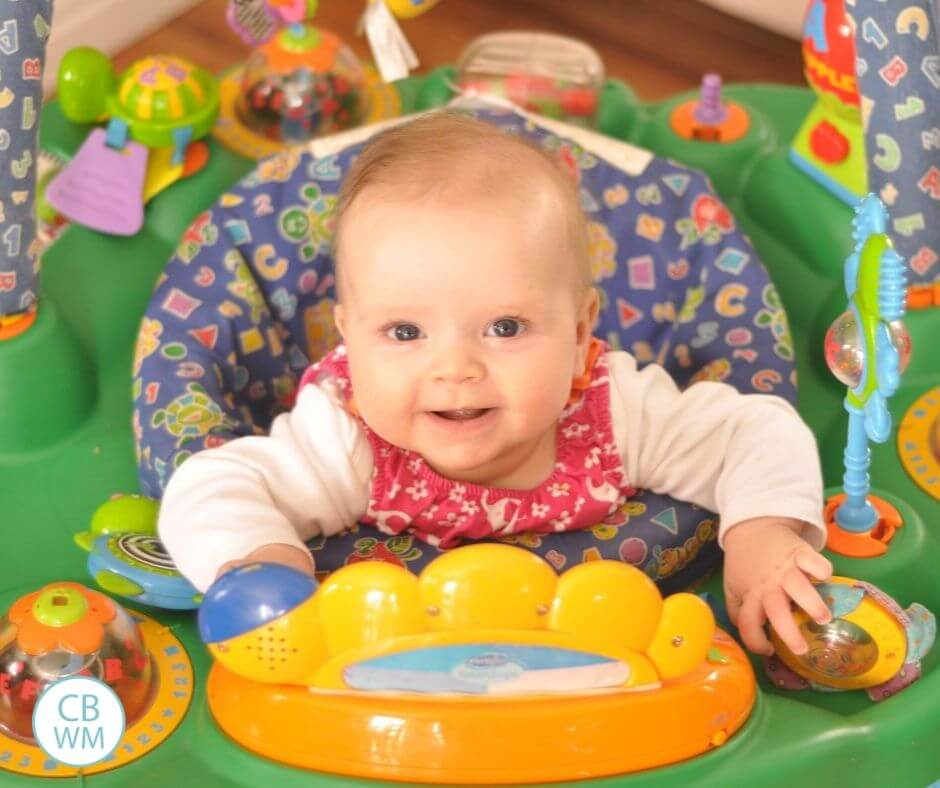 5 month old baby girl playing in an exersaucer