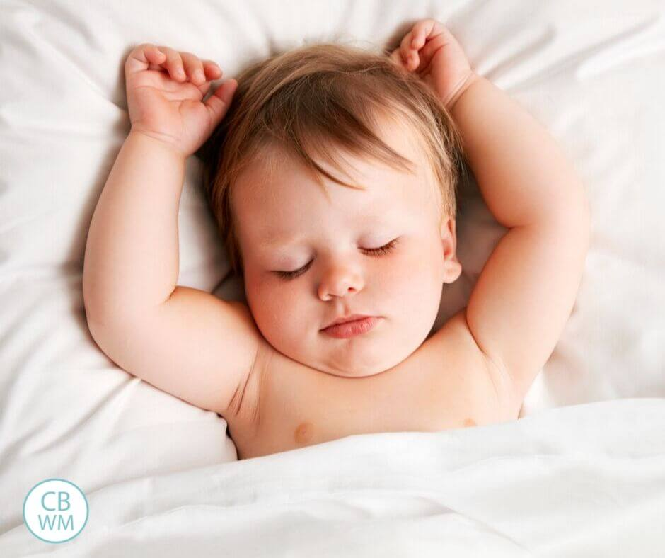 Sleeping baby on white linens