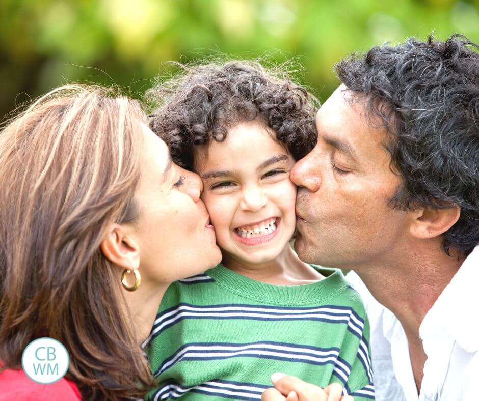 Parents kissing kid's cheek
