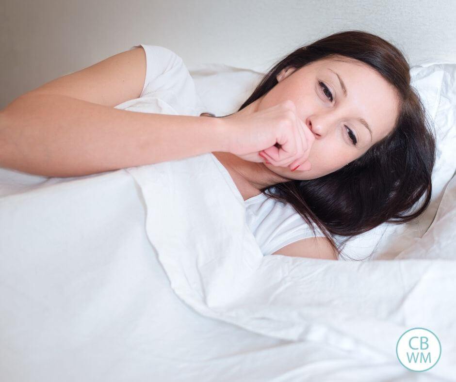 Woman sick in bed coughing