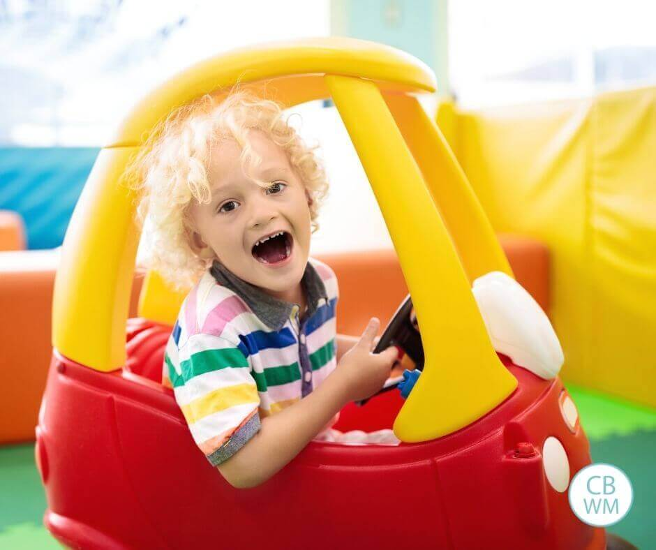 Boy playing in a Cozy Coupe
