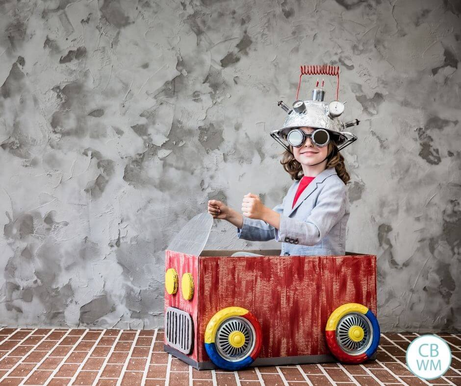 Child playing in cardboard car