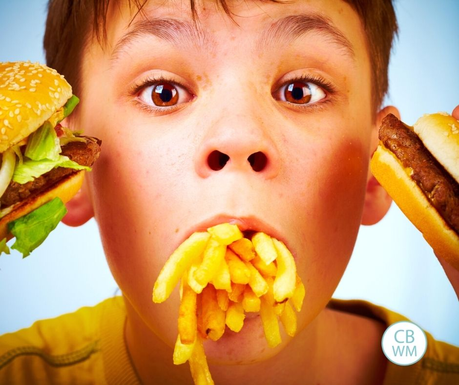 Child eating a lot of food and holding food up to face
