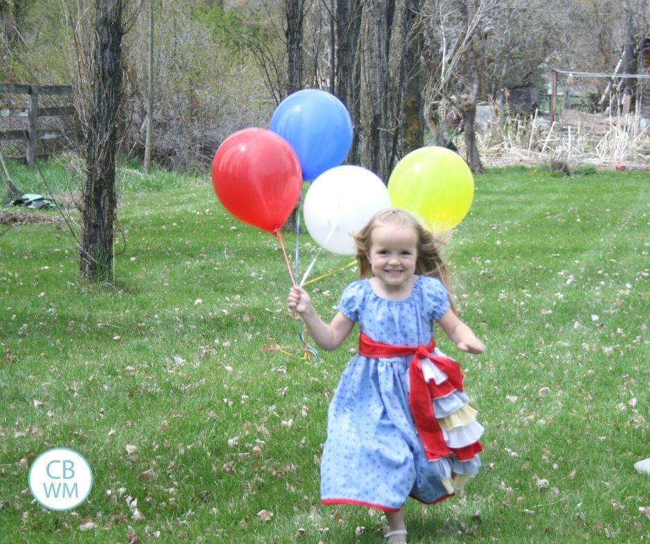 4 year old Kaitlyn running toward camera with balloons