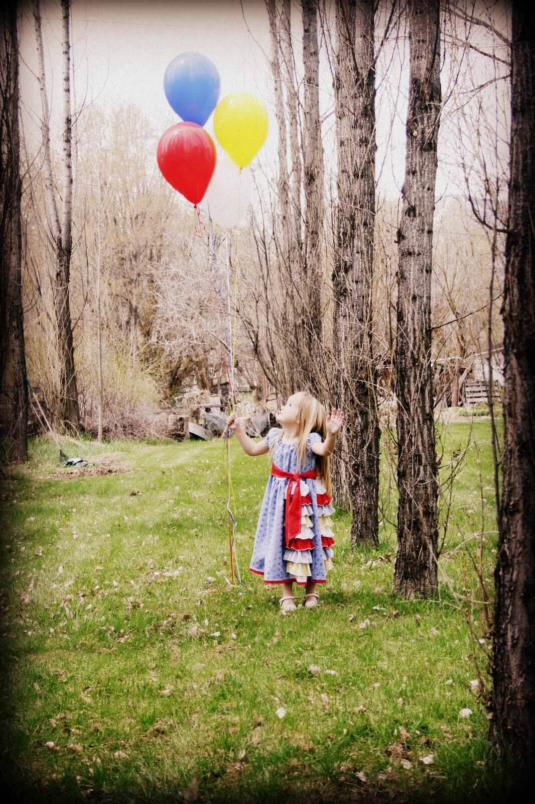 4 year old Kaitlyn holding 4 balloons