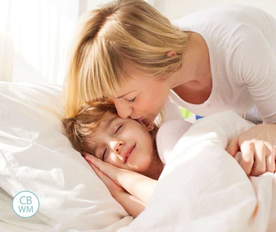 Child sleeping with sun in the room. Mom kissing cheek.