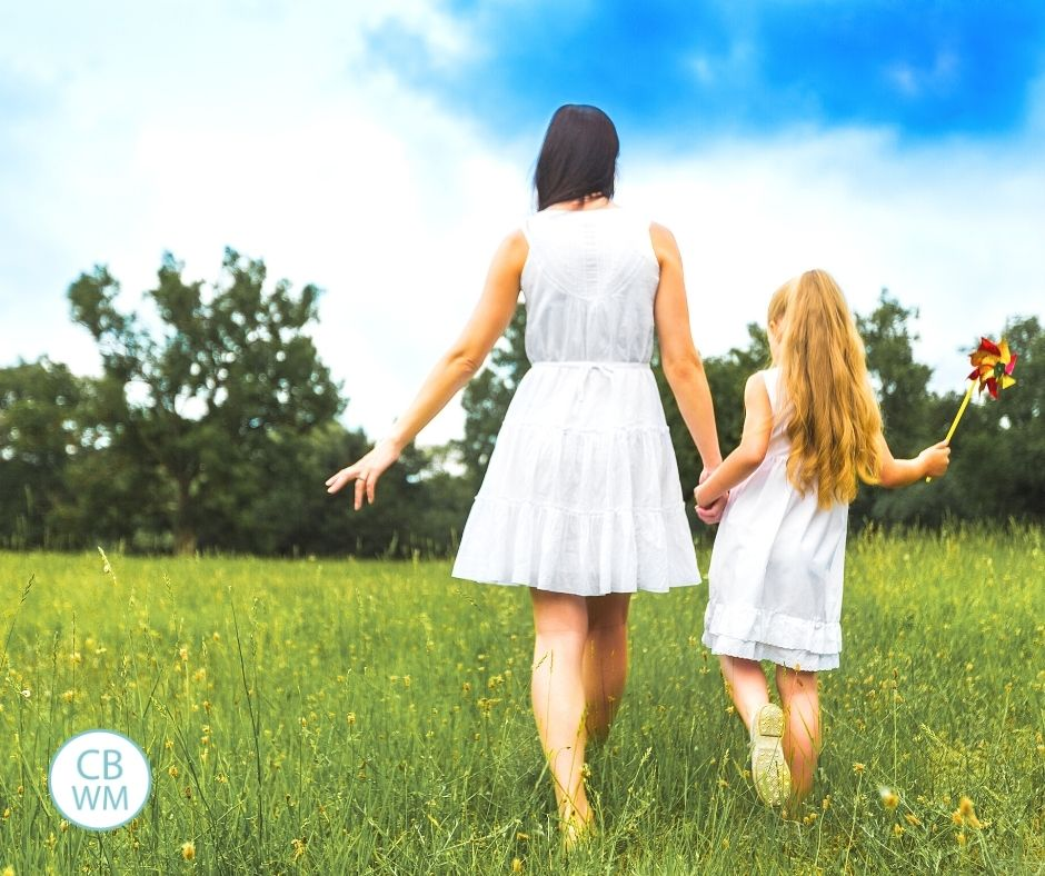 Mom and daughter walking through field