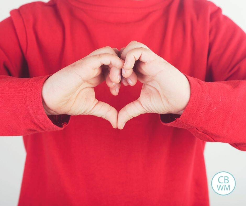 Child making a heart with hands