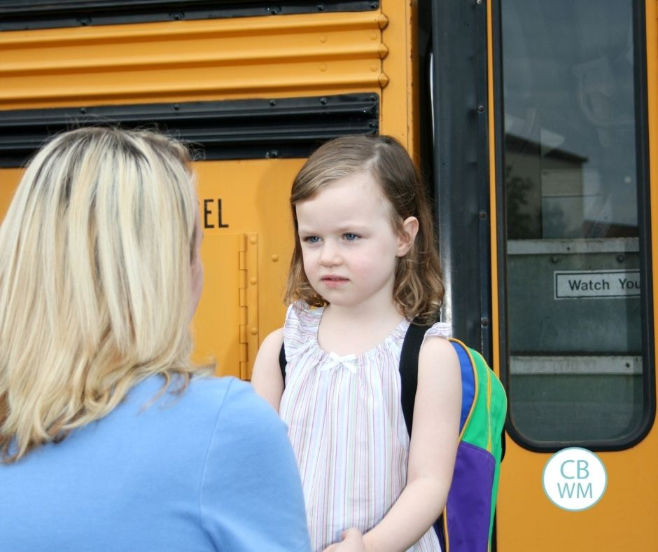 Mom correcting child before she gets on the bus