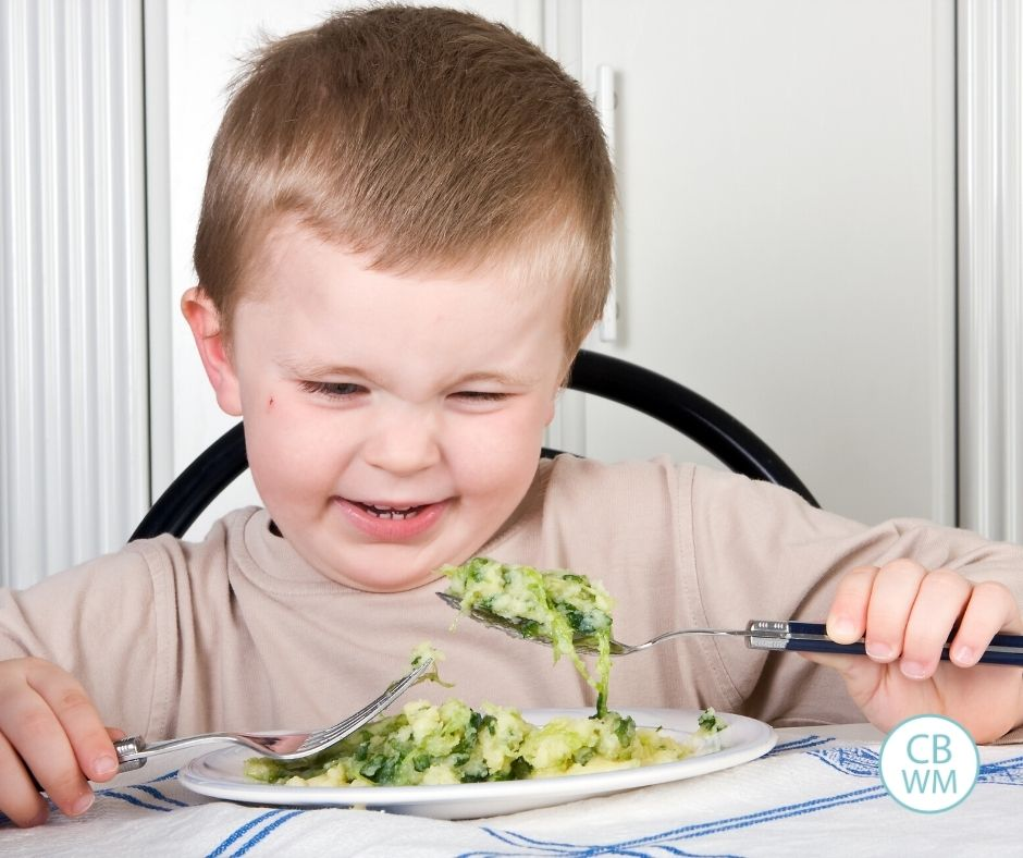 Child being picky about eating broccoli at the dinner table