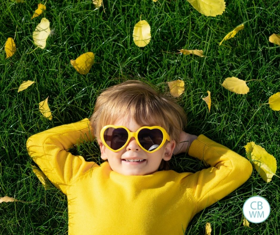 Child lying on the grass wearing a yellow sweater and yellow heart glasses