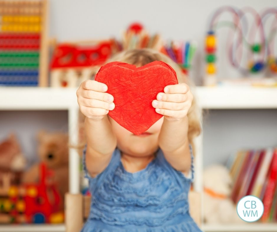 Child holding up a red heart