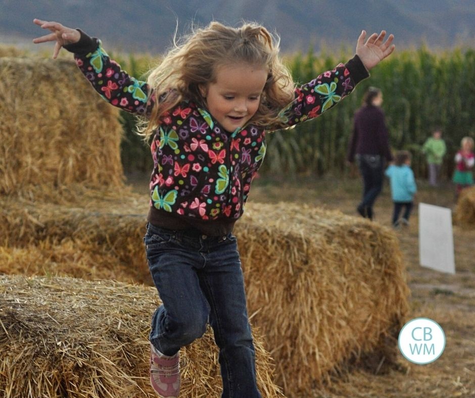 4.5 year old Kaitlyn jumping of a pile of straw bales