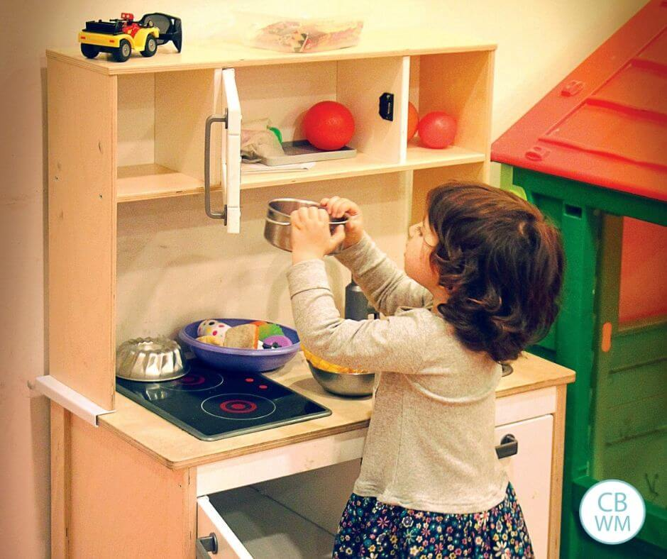 Girl playing with a toy kitchen