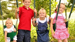 Four children sitting on swings