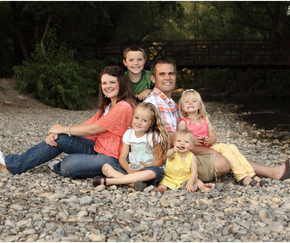 Family of 6 sitting on river rock