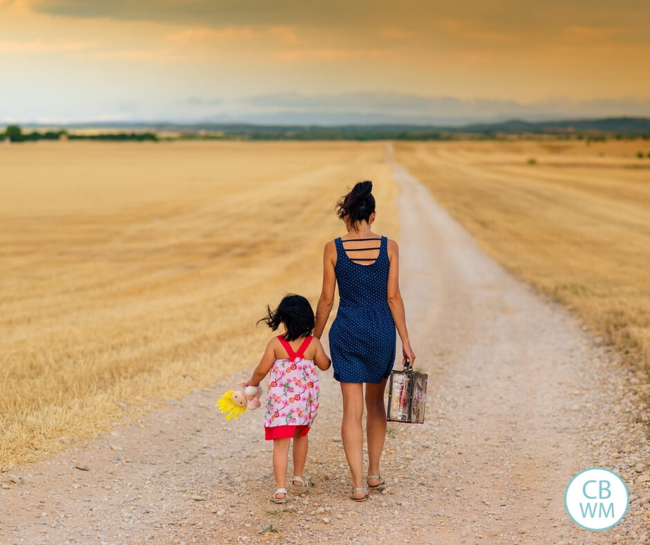 mother and daughter walking along a dirt road