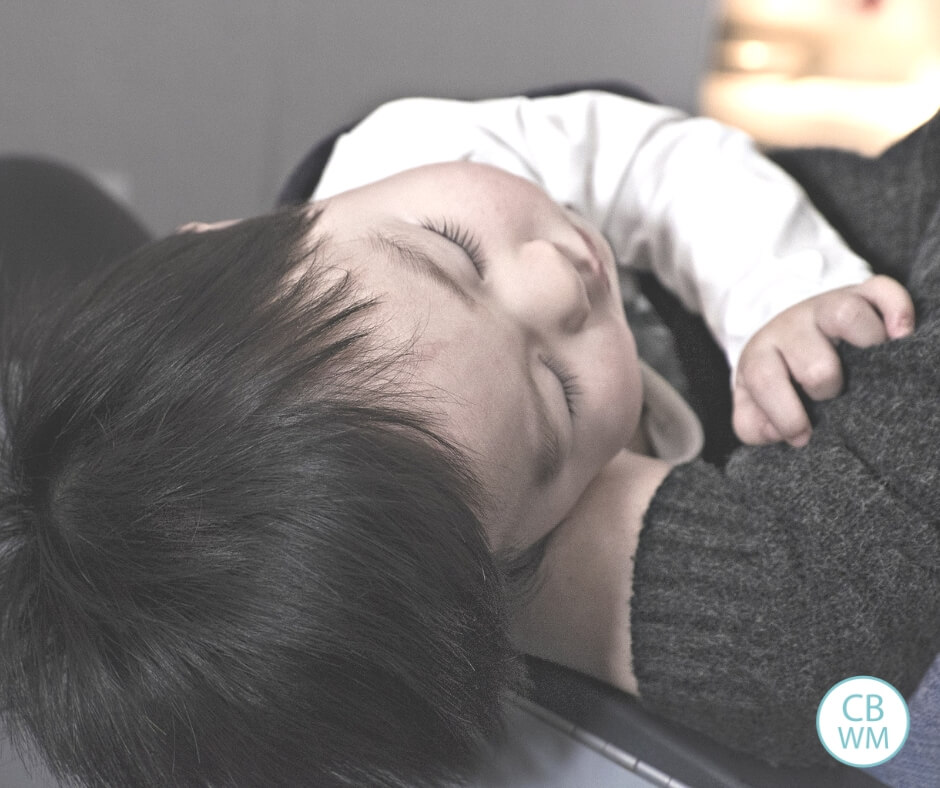 baby sleeping in the arms of an adult