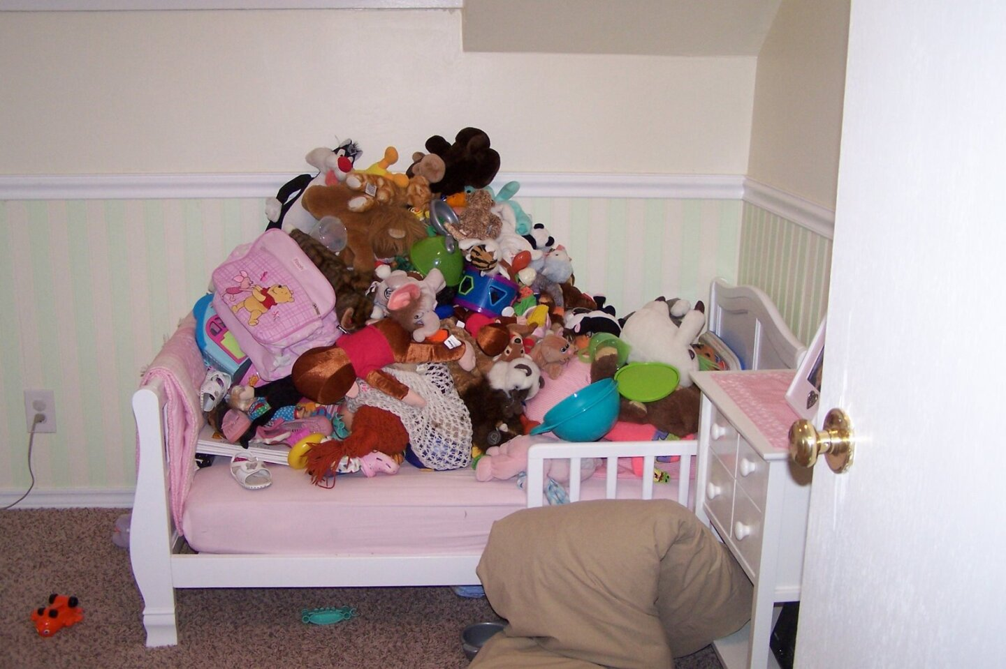 Pile of toys on a toddler bed