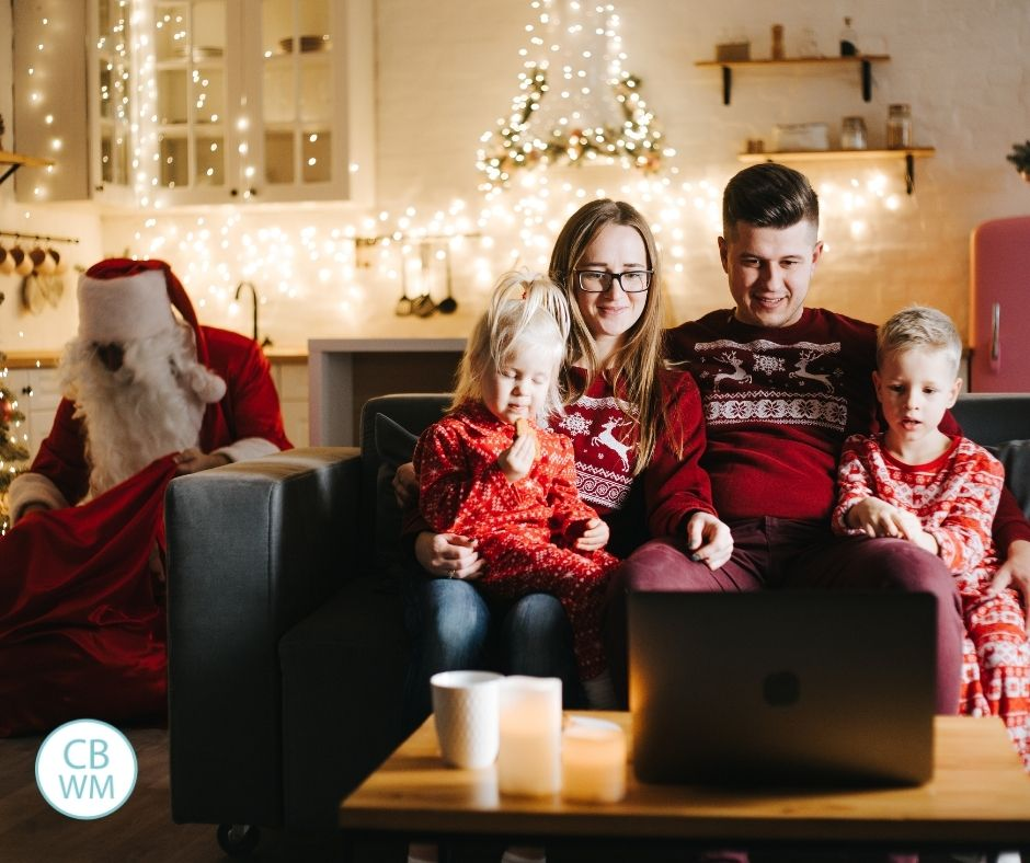 Family watching Christmas movies together with Santa behind them