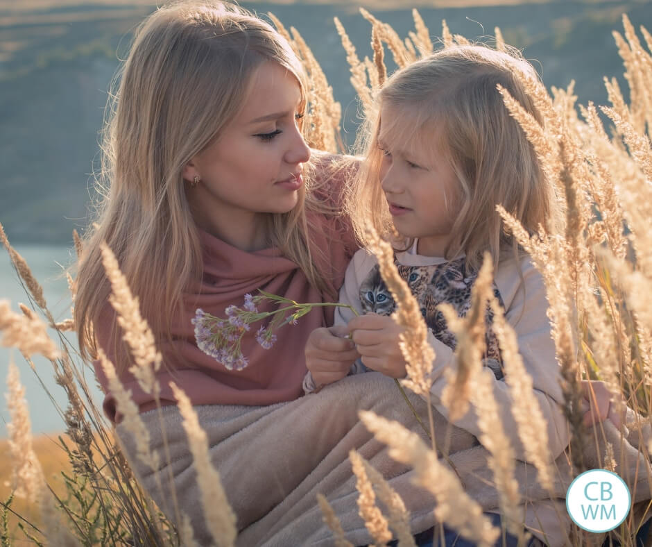 Mother and daughter sitting in a wheat field