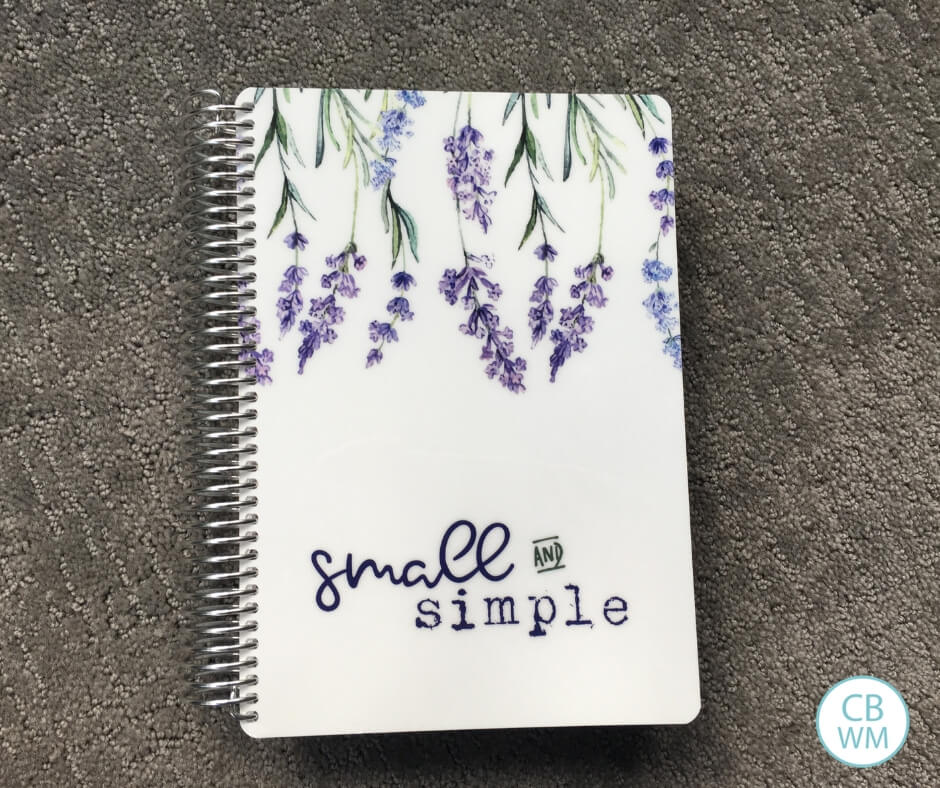 "Spiral bound planner titled ""Small and Simple"" on a gray background."
