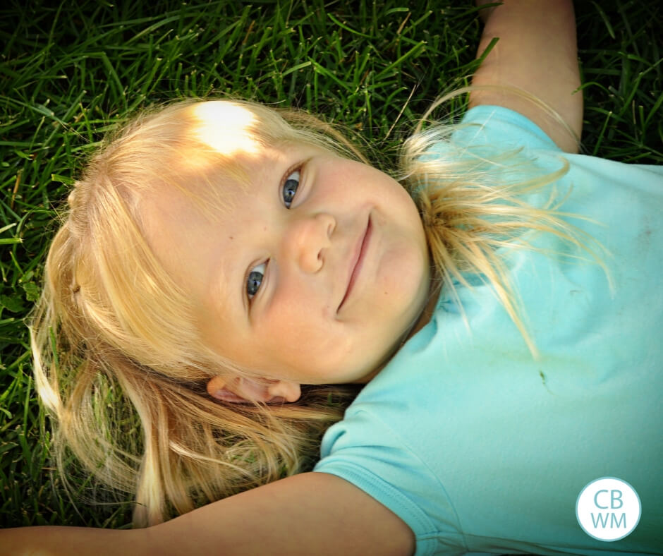 three year old girl with blonde hair lying on the grass