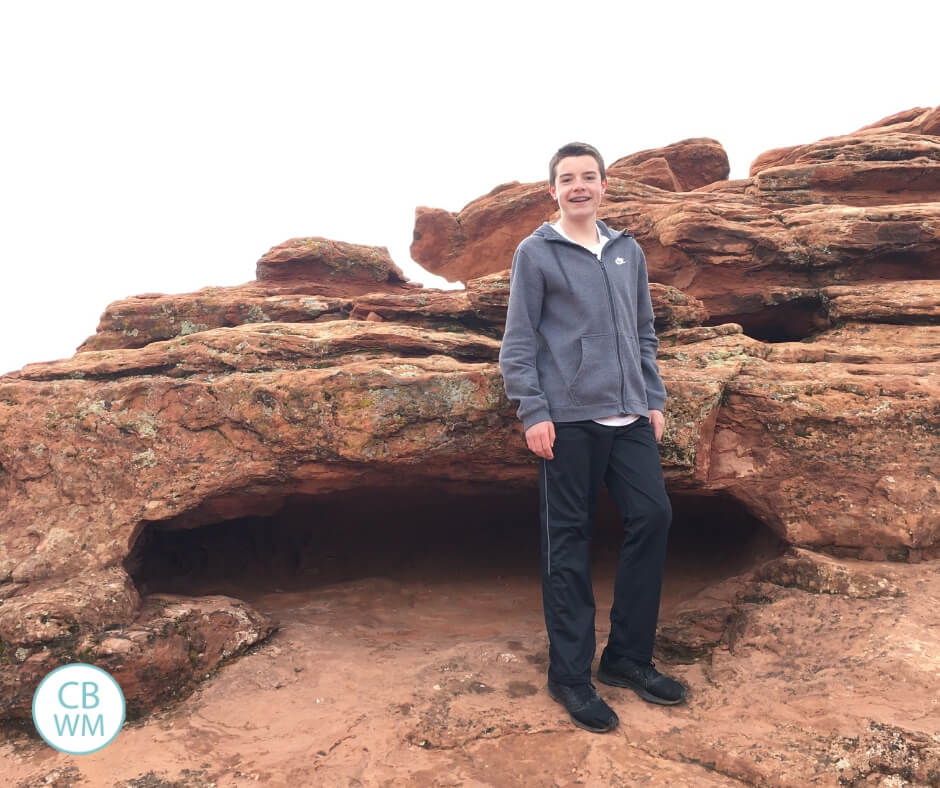 Teenage boy standing on red rock