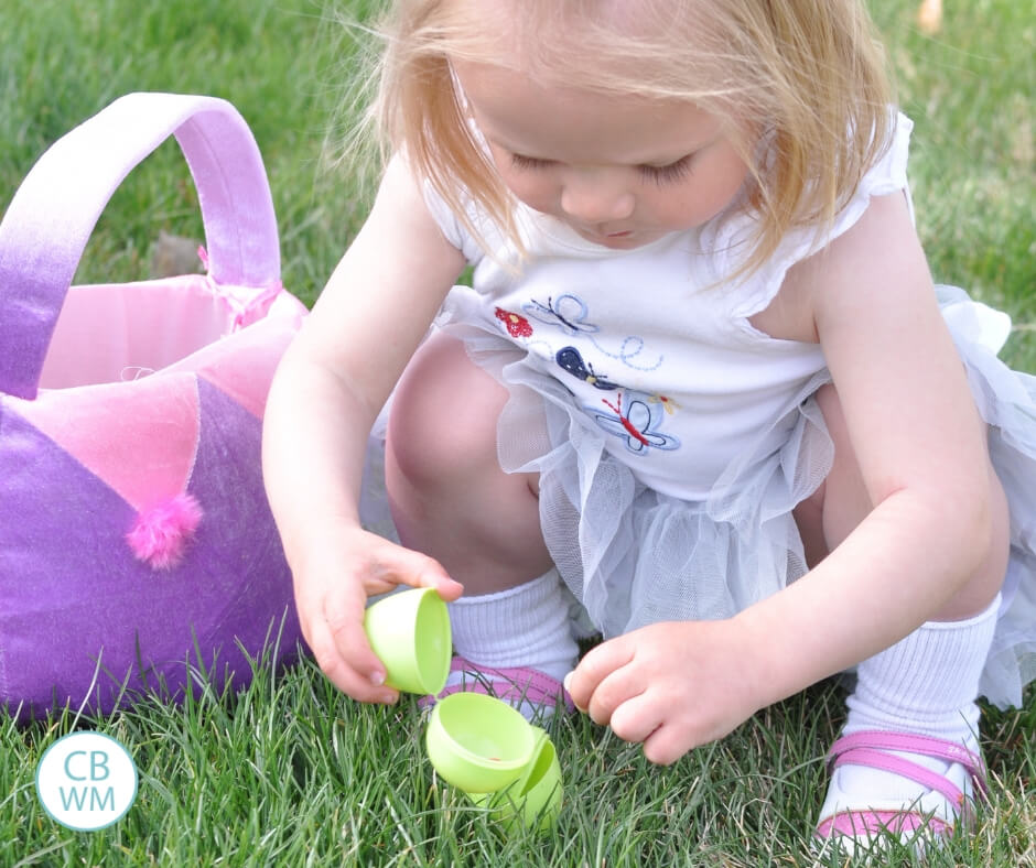 toddler opening Easter egg on the grass next to an Easter basket