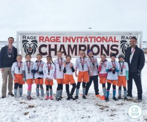 Soccer team standing in front of a championship sign