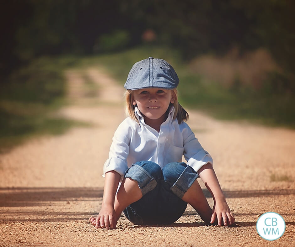 Boy sitting on a dirt road facing the camera