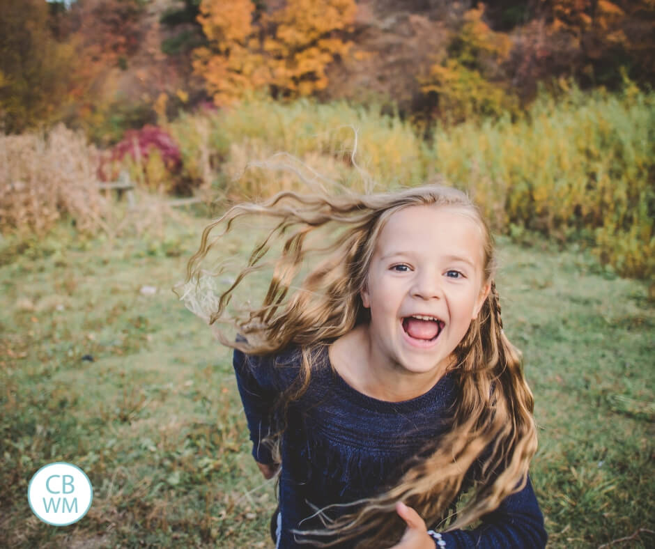 Girl running toward the camera with fall foliage behind her.